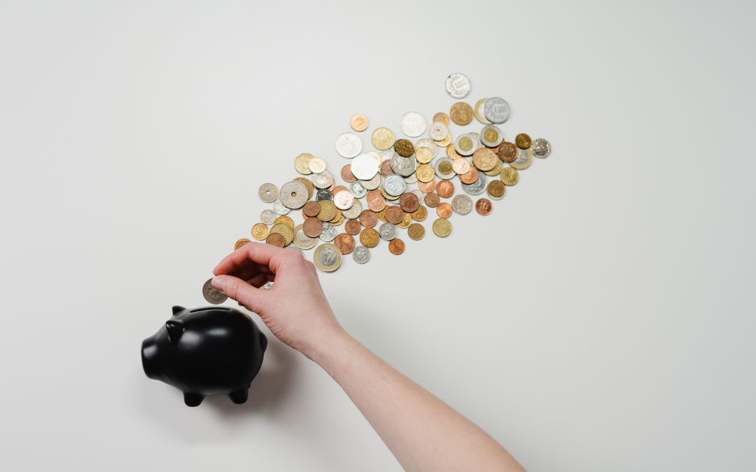 a hand adding a coin to a piggy bank on a background of coins